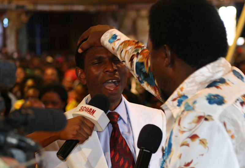 """FILE - In this Sunday, Sept. 15, 2013 file photo, T.B. Joshua lays his hand on the head of a worshipper during a service at the Synagogue, Church of All Nations, in Lagos Nigeria. T.B. Joshua's Synagogue, Church of All Nations has branches around the world, and a recent YouTube video even credits him with predicting the disappearance of Malaysian Airlines Flight MH370. Joshua is one of the best-known preachers in Africa and among the most profitable in Nigeria, the go-to faith healer and spiritual guide for leaders such as the late Ghanaian president John Atta Mills, Malawian president Joyce Banda and former Zimbabwean prime minister Morgan Tsvangirai. The man who says he comes from the poor village of Arigidi is worth between $10 and $15 million based on assets, according to Forbes magazine, which in 2011 estimated his personal wealth. The church holds some 15,000 people with outside tents for the overflow and Sunday services are beamed worldwide. Yet critics say this wildly popular televangelist hinders efforts to curtail the spread of HIV and tuberculosis with testimonies by church-goers that faith and his holy water can cure both. He is also accused of taking advantage of his followers and tightly controlling those closest to him, who call him """"Daddy.""""(AP Photo/Carley Petesch, file)"""