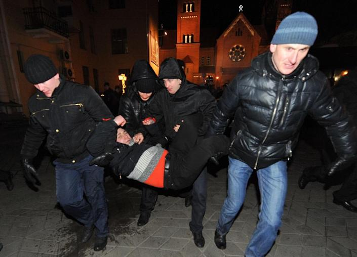 Belarusian police carry a man detained during an unauthorized rally in Minsk, on December 19, 2011 (AFP Photo/Victor Drachev)