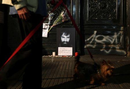 A man walks his dog past a portrait of Santiago Maldonado, a protester who went missing since security forces clashed with indigenous activists in Patagonia on August 1, 2017, placed at the entrance of a  judicial morgue in Buenos Aires, Argentina October 20, 2017.  REUTERS/Marcos Brindicci