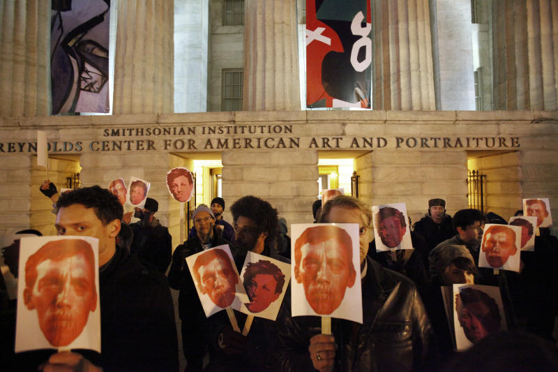 FILE - In this Dec. 2, 2010, file photo, protesters hold masks in support of artist David Wojnarowicz on the steps of the Smithsonian's National Portrait Gallery, after a video by Wojnarowicz was removed from exhibition at the museum, in Washington. The Andy Warhol Foundation said Monday, Dec. 13, 2010, it will withhold future funding to the Smithsonian Institution unless a video removed from the gallery after a Catholic group complained is restored.(AP Photo/Jacquelyn Martin, File)