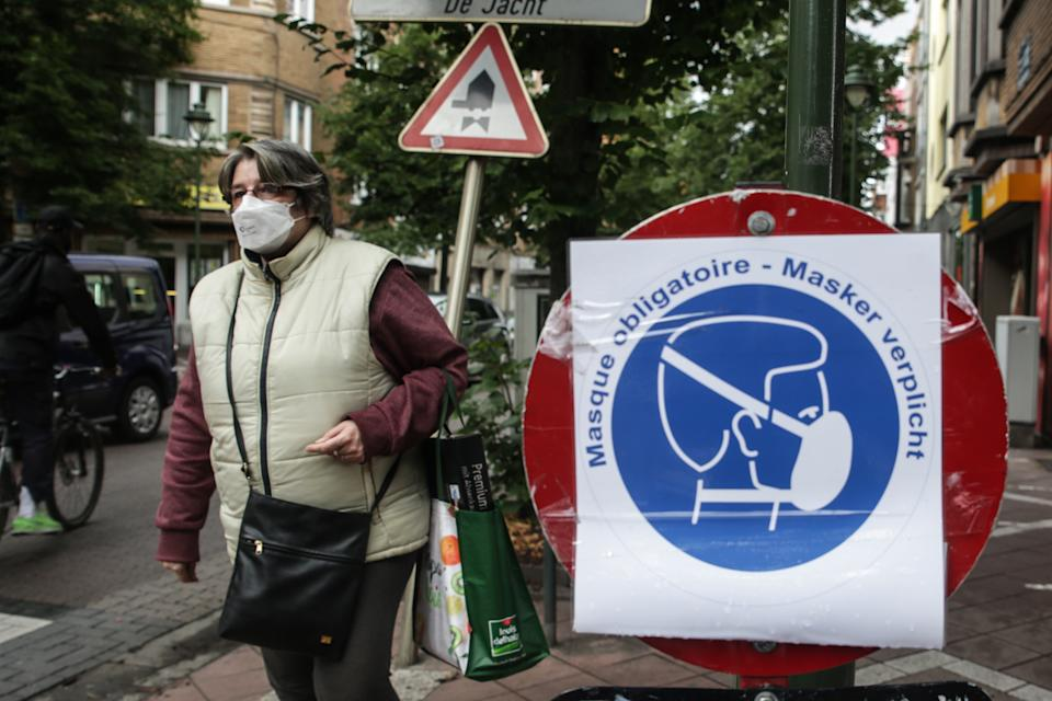 A woman wearing a face mask walks by a board bearing sanitary measures, on July 10 2020 in Brussels, amid the crisis linked with the Covid-19 pandemic caused by the novel coronavirus. - Wearing a face mask will become mandatory on July 10, 2020 in Belgian shops, cinemas, entertainment venues and other indoor spaces, the government announced. (Photo by Aris Oikonomou / AFP) (Photo by ARIS OIKONOMOU/AFP via Getty Images)