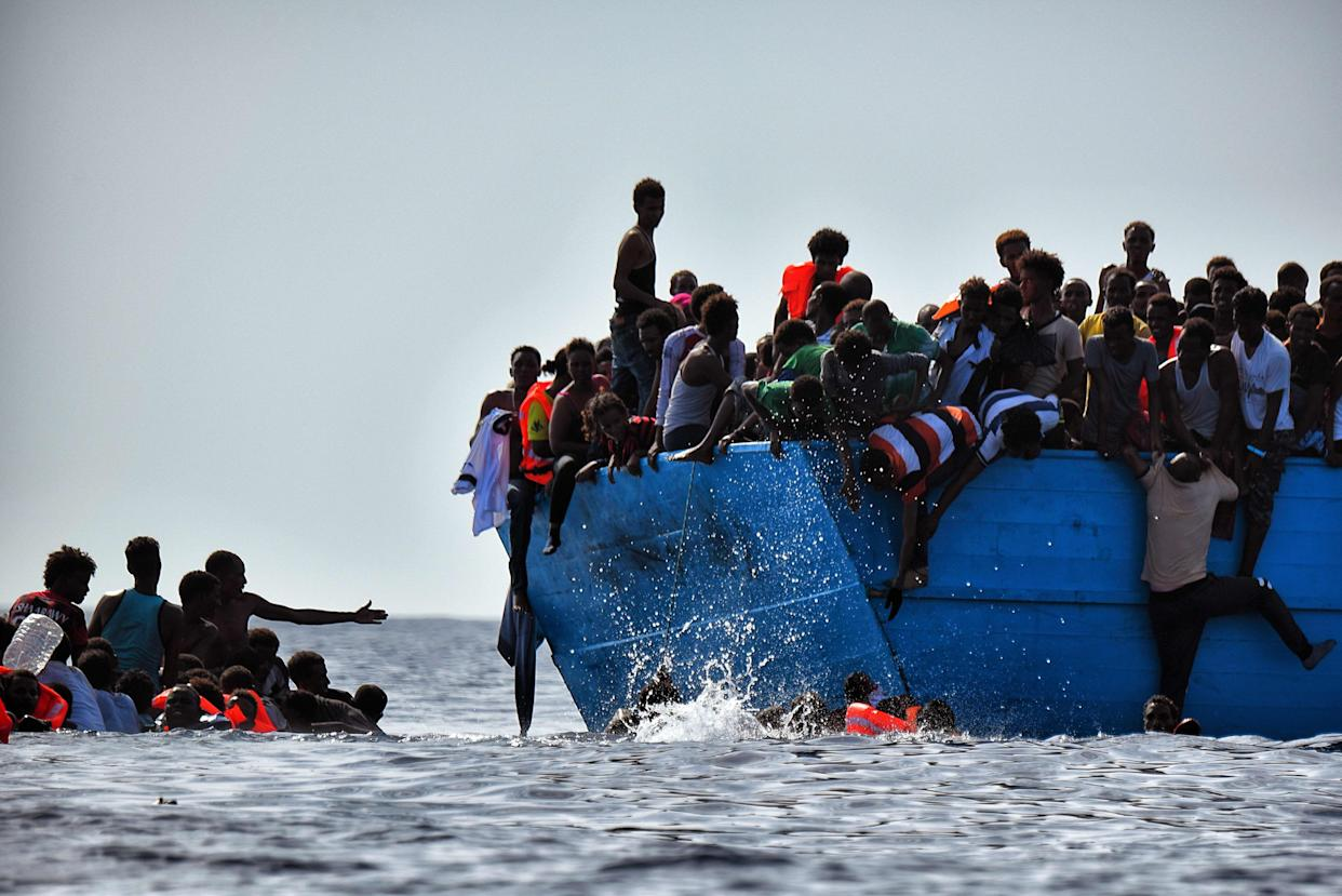 Migrants hang from a boat as they wait to be rescued as they drift in the Mediterranean Sea, some 12 nautical miles north of Libya, on October 4, 2016. At least 1,800 migrants were rescued off the Libyan coast, the Italian coastguard announced, adding that similar operations were underway around 15 other overloaded vessels. / AFP / ARIS MESSINIS (Photo credit should read ARIS MESSINIS/AFP/Getty Images)
