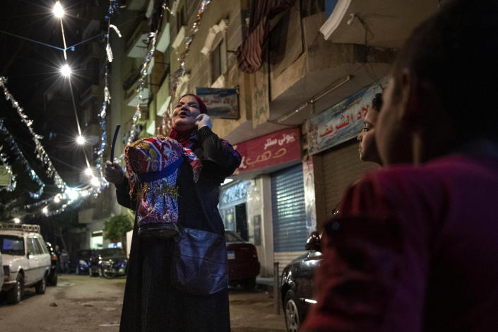 """Hajja Dalal, a 46-year-old """"mesaharati,"""" or dawn caller, wakes people up for a meal before sunrise, during the Islamic holy month of Ramadan, in Cairo, Egypt, Wednesday, April 29, 2020. (AP Photo/Nariman El-Mofty)"""