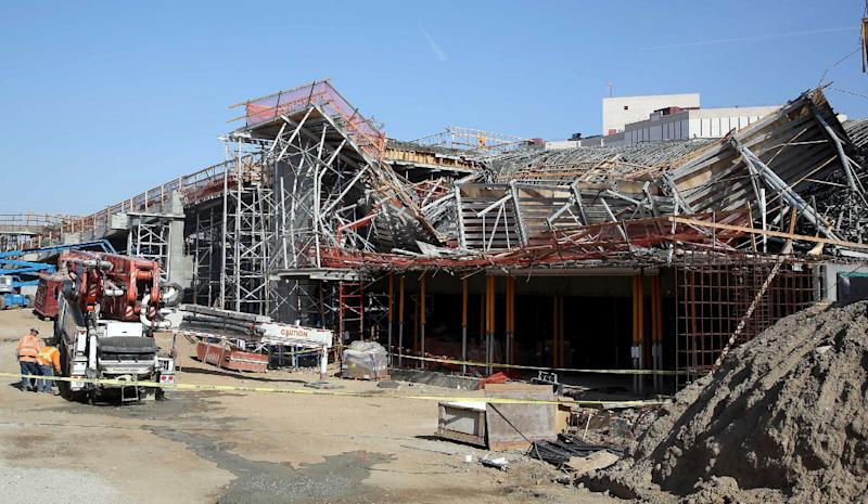 Men work near the site where section of a parking structure under construction collapsed Friday March 28, 2014 in Los Angeles. No one was trapped or hurt, authorities said. (AP Photo/Nick Ut)