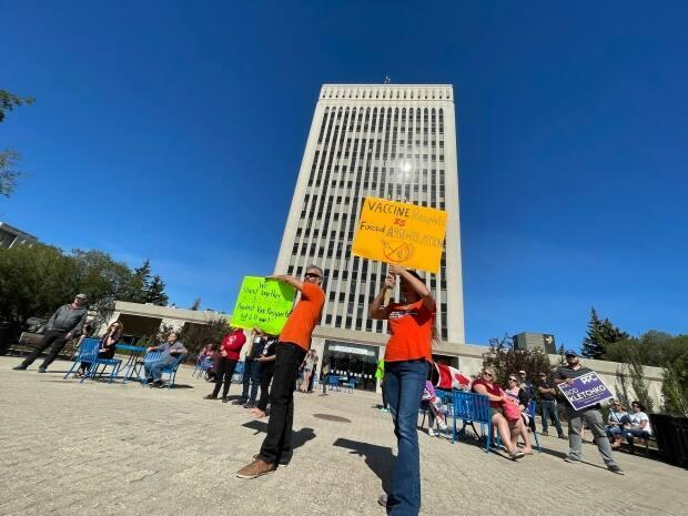 Approximately 100 anti-vaccine passport protesters gathered in front of city hall Wednesday afternoon to voice their opposition with signs and speeches. (Richard Agecoutay/CBC - image credit)