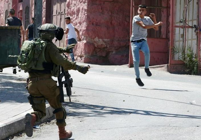 A Palestinian protester hurls stones at an Israeli soldier during clashes following Friday prayers in the West Bank town of Hebron