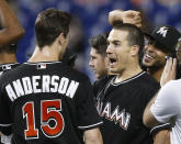 Miami Marlins catcher J.T. Realmuto, second from left, is congratulated by teammates after he drove in the winning run during the 10th inning against the Washington Nationals in a baseball game Saturday, July 28, 2018, in Miami. The Marlins won 2-1. (AP Photo/Brynn Anderson)