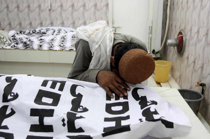 A Pakistani mourns over a dead body of his family member who is killed in a bomb attack, at a mortuary in Quetta, Pakistan, Friday, July 13, 2018. Underscoring the security threat, two bombs exploded Friday killing many people in the latest election related violence to hit Pakistan. The first bomb that killed four people exploded in northwest Pakistan near the election rally of a senior politician from an Islamist party who is running for parliament from the northwestern town of Bannu. (AP Photo/Arshad Butt)