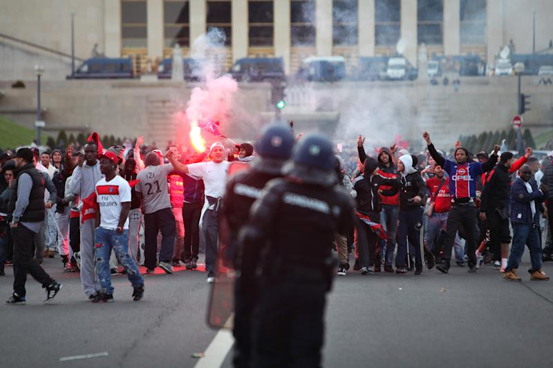 Paris Saint Germain's supporters face riot police officers during clashes after the celebration of PSG's French League title, in Paris, Monday, May 13, 2013. Paris Saint-Germain clinched its first French league title since 1994 by defeating Lyon 1-0 on Sunday. PSG has now an unassailable seven-point lead at the top of the standings. With just two rounds left, second-place Marseille can no longer catch its fierce rival. (AP Photo/Thibault Camus)