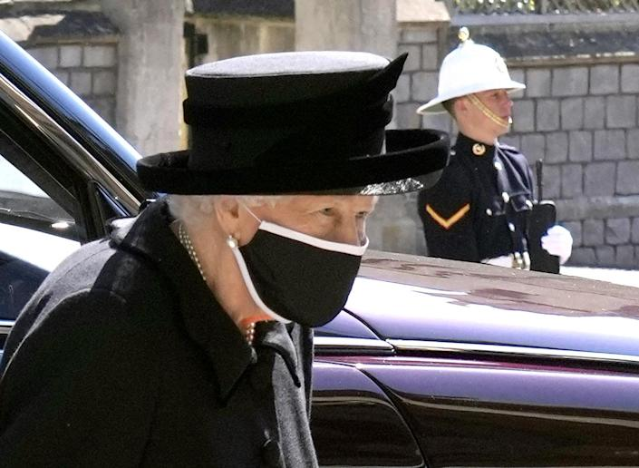 Queen Elizabeth II next to a car at Windsor Castle while a military member stands nearby.