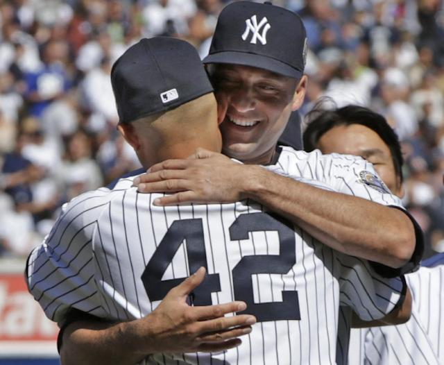 New York Yankees shortstop Derek Jeter embraces relief pitcher Mariano Rivera (42) during a pregame ceremony honoring Rivera at Yankee Stadium before a baseball game against the San Francisco Giants, Sunday, Sept. 22, 2013, in New York. Rivera, a 13-time All-Star, is retiring at the end of this season. (AP Photo/Kathy Willens)