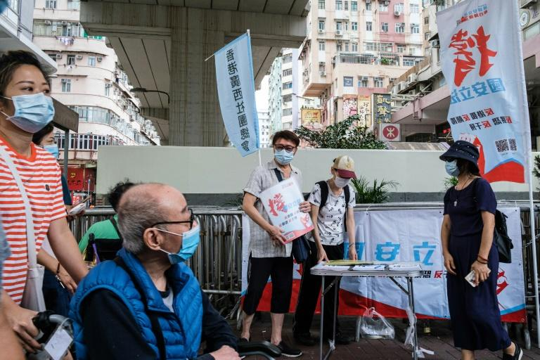 People stand at a booth where passersby can give their signatures in support of a new security law in Hong Kong (AFP Photo/Anthony WALLACE)