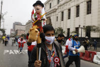 A supporter of President-elect Pedro Castillo carries a doll in his likeness on his Inauguration Day in Lima, Peru, Wednesday, July 28, 2021. (AP Photo/Guadalupe Pardo)