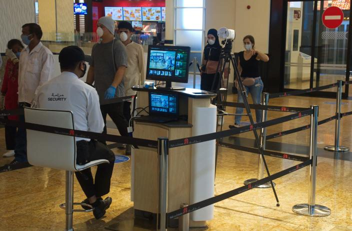 FILE - In this May 27, 2020, file photo, a security guard watches an infrared scanner monitoring incoming customers for fevers at Mall of the Emirates in Dubai, United Arab Emirates. Efforts by the United Arab Emirates to fight the coronavirus have renewed questions about mass surveillance in this U.S.-allied federation of seven sheikhdoms.(AP Photo/Jon Gambrell, File)
