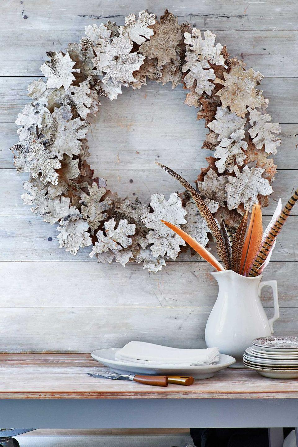 """<p>Birch bark is the key to these autumn """"leaves."""" <strong><br></strong></p><p><strong>Make the wreath</strong><strong>:</strong> You'll need twenty-four 6 3/4""""W x 20 1/2""""L sheets of birch bark, a 20-inch-diameter <a href=""""https://www.amazon.com/Panacea-36003-Wreath-Frame-Green/dp/B004BPTGUU/?linkCode=ogi&tag=syn-yahoo-20&ascsubtag=%5Bartid%7C10050.g.2610%5Bsrc%7Cyahoo-us"""" rel=""""nofollow noopener"""" target=""""_blank"""" data-ylk=""""slk:foam wreath form"""" class=""""link rapid-noclick-resp"""">foam wreath form</a>, and 45 small wooden cubes to act as risers<em>. </em>First, print and cut out our <a href=""""http://clv.h-cdn.co/assets/cm/15/27/559438a2f0fa5_-_leaf-templates-1113.pdf"""" rel=""""nofollow noopener"""" target=""""_blank"""" data-ylk=""""slk:oak- and maple-leaf templates"""" class=""""link rapid-noclick-resp"""">oak- and maple-leaf templates</a>. Trace 75 assorted leaves onto the birch-bark sheets, and cut out. Varying the leaf type, hot-glue 30 leaves onto the wreath form. Then, hot-glue a wooden cube onto the back of each remaining leaf. Using our photo as a guide, hot-glue the cube-backed leaves atop the original leaves. </p>"""