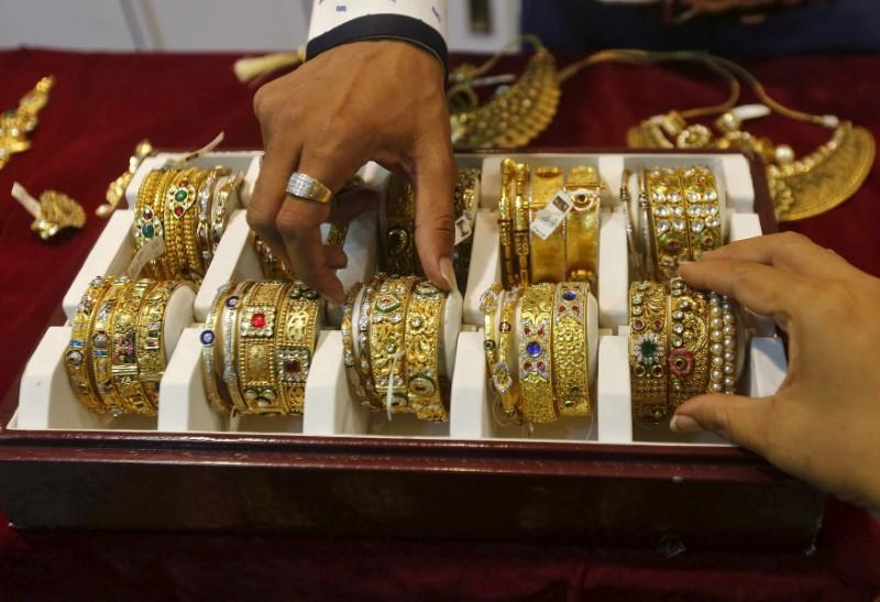 A salesman helps a customer to select gold bangles at a jewelry showroom in Mumbai