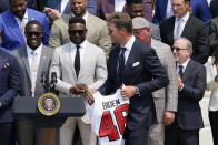 Tampa Bay Buccaneers quarterback Tom Brady carries a jersey for President Joe Biden during a ceremony on the South Lawn of the White House, in Washington, Tuesday, July 20, 2021, the president honored the Super Bowl Champion Tampa Bay Buccaneers for their Super Bowl LV victory. (AP Photo/Andrew Harnik)