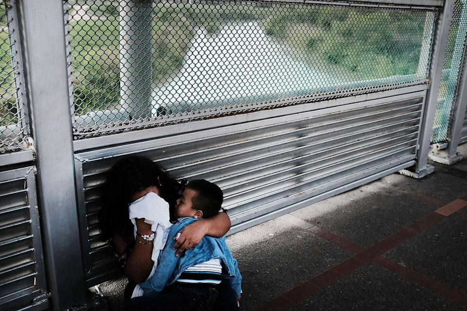 <p>A Honduran woman cries while holding her child after being denied entry at the border in Brownsville, Texas. </p>