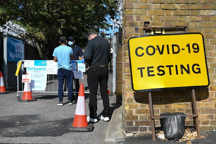 People queue up outside a coronavirus testing centre offering walk-in appointments in east London. (Getty)