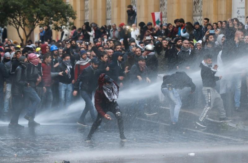 Demonstrators are hit by water canon during a protest against a ruling elite accused of steering Lebanon towards economic crisis in Beirut
