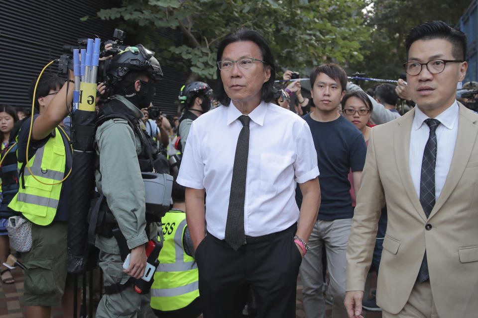 In this Monday, Nov. 25, 2019 photo, lawyer Daniel Wong Kwok-tung, center, arrives at the Polytechnic University to meet the protesters in Hong Kong. Hong Kong national security police on Thursday, Jan. 14, 2021, arrested a lawyer and 10 others on suspicion of helping 12 Hong Kongers try to flee the city, local media reported in the latest arrests in an ongoing crackdown on dissent. Wong, a member of the city's Democratic Party, is known for providing legal assistance to hundreds of protesters arrested during the anti-government protests in Hong Kong in 2019. (AP Photo/Kin Cheung)