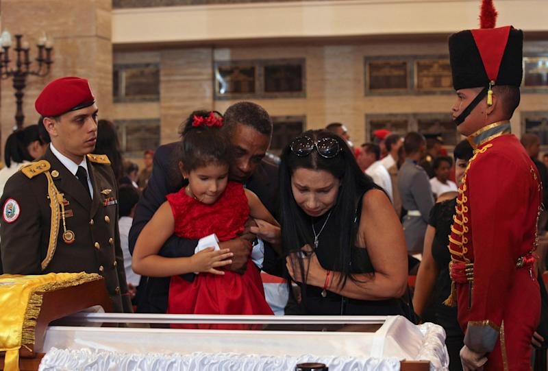 In this photo provided by Miraflores Presidential Press Office, a man helps a girl to look into the glass-topped casket containing the remains of Venezuela's late President Hugo Chavez lying in state at the military academy in Caracas, Venezuela, Thursday, March 7, 2013.  While Venezuela remains deeply divided over the country's future, the multitudes who reached the president's coffin were united in grief and admiration for a man many considered a father figure. Chavez died on March 5 after a nearly two-year bout with cancer.(AP Photo/Miraflores Press Office)