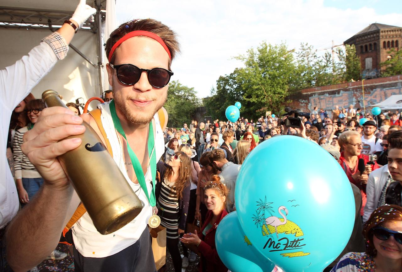 "BERLIN, GERMANY - JULY 21: A member of the winning team, Jam FM, holds the ""Golden Club Mate"" trophe after winning the second annual Hipster Olympics on July 21, 2012 in Berlin, Germany. With events such as the ""Horn-Rimmed Glasses Throw,"" ""Skinny Jeans Tug-O-War,"" ""Vinyl Record Spinning Contest"" and ""Cloth Tote Sack Race,"" the Hipster Olympics both mocks and celebrates the Hipster subculture, which some critics claim could never be accurately defined and others that it never existed in the first place. The imprecise nature of determining what makes one a member means that the symptomatic elements of adherants to the group vary in each country, but the archetype of the version in Berlin, one of the more popular locations for those following its lifestyle, along with London and Brooklyn, includes a penchant for canvas tote bags, the carbonated yerba mate drink Club Mate, analogue film cameras, asymmetrical haircuts, 80s neon fashion, and, allegedly, a heavy dose of irony. To some in Berlin, members of the hipster ""movement"" have replaced a former unwanted identity in gentrifying neighborhoods, the Yuppie, for targets of criticism, as landlords raise rents in the areas to which they relocate, particularly the up-and-coming neighborhood of Neukoelln.  (Photo by Adam Berry/Getty Images)"