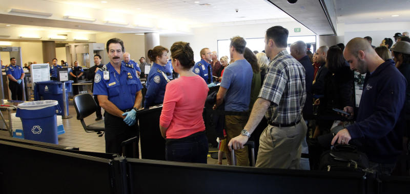 TSA officers and passengers at Los Angeles International Airport, observe a moment of silence Friday Nov. 8, 2013, to honor the Transportation Security Administration officer Gerardo Hernandez, killed by a gunman at Los Angeles International Airport a week ago.(AP Photo/Nick Ut)