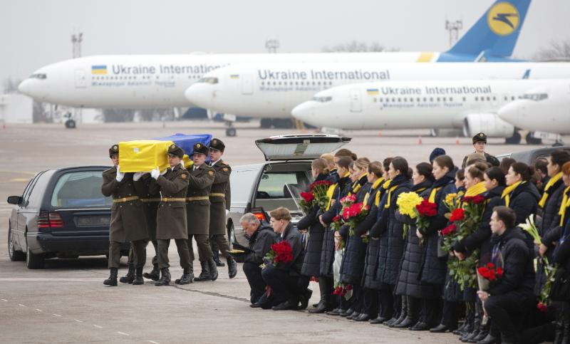 In this photo provided by the Ukrainian Presidential Press Office, honor guard carry a coffin of the one of the eleven Ukrainian victims of the Ukrainian 737-800 plane that crashed on the outskirts of Tehran, at Borispil international airport outside Kyiv, Ukraine, Sunday, Jan. 19, 2020. An Ukrainian passenger jet carrying 176 people has crashed just minutes after taking off from the Iranian capital's main airport on Jan. 8, 2020. (Ukrainian Presidential Press Office via AP)