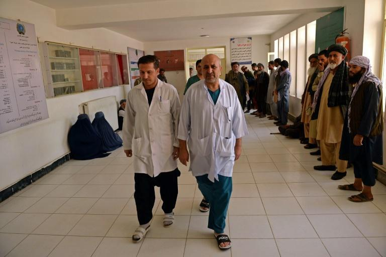 Doctors walk inside a regional hospital where victims of October 8 suicide bombing at the Gozar-e-Sayed mosque are being treated (AFP/Hoshang Hashimi)