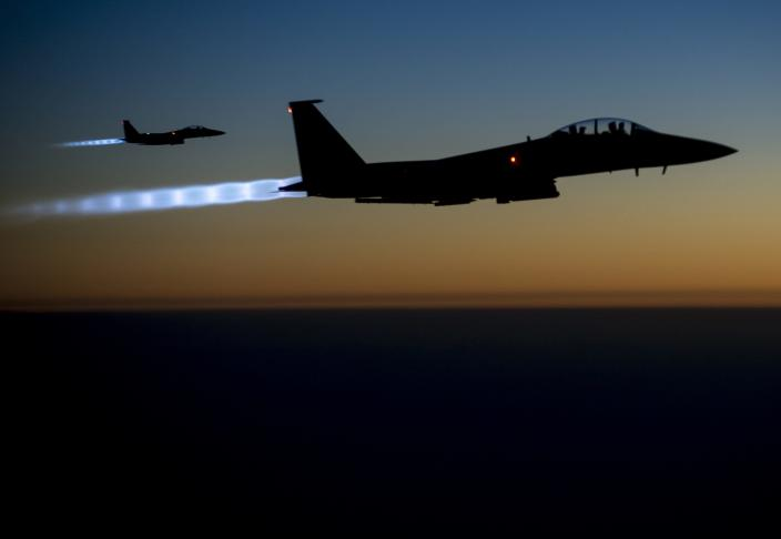 A pair of U.S. Air Force F-15E Strike Eagles fly over northern Iraq after conducting airstrikes in Syria, in this U.S. Air Force handout photo taken early in the morning of September 23, 2014. These aircraft were part of a large coalition strike package that was the first to strike ISIL targets in Syria. At least 14 Islamic State fighters were killed in air strikes by U.S.-led forces overnight in northeast Syria, a group monitoring the war said on September 25, 2014, and the Syrian air force bombed rebel areas in the west of the country. REUTERS/U.S. Air Force/Senior Airman Matthew Bruch/Handout (IRAQ - Tags: POLITICS CONFLICT TPX IMAGES OF THE DAY) FOR EDITORIAL USE ONLY. NOT FOR SALE FOR MARKETING OR ADVERTISING CAMPAIGNS. THIS IMAGE HAS BEEN SUPPLIED BY A THIRD PARTY. IT IS DISTRIBUTED, EXACTLY AS RECEIVED BY REUTERS, AS A SERVICE TO CLIENTS