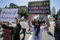 """Protestors march at a rally against Asian hate crimes past the Los Angeles Federal Building in downtown Los Angeles , Saturday, March 27, 2021. The gathered crowd demanded justice for the victims of the Atlanta spa shooting and for an end to racism, xenophobia and misogyny. The """"LA vs. Hate"""" initiative encourages people to call 211 if they are victims or witness an incident of hate. (AP Photo/Damian Dovarganes)"""