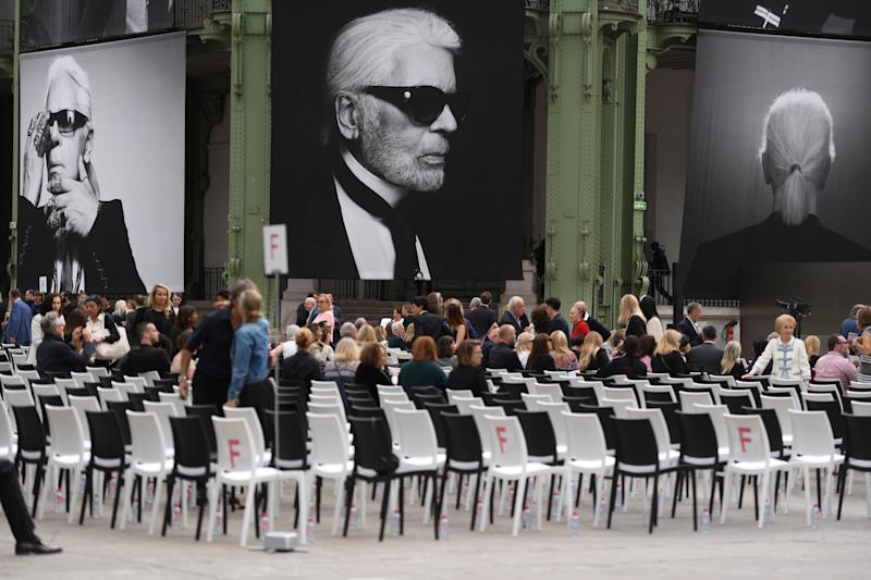"People arrive at the Grand Palais, decorated with photographs picturing late German fashion designer Karl Lagerfeld, at the start of the ""Karl For Ever"" event to honour him in Paris, on June 20, 2019. - The late designer for the French label Chanel, Karl Lagerfeld, died at the age of 85, on February 19, 2019, in Paris. (Photo by CHRISTOPHE ARCHAMBAULT / AFP) (Photo credit should read CHRISTOPHE ARCHAMBAULT/AFP/Getty Images)"