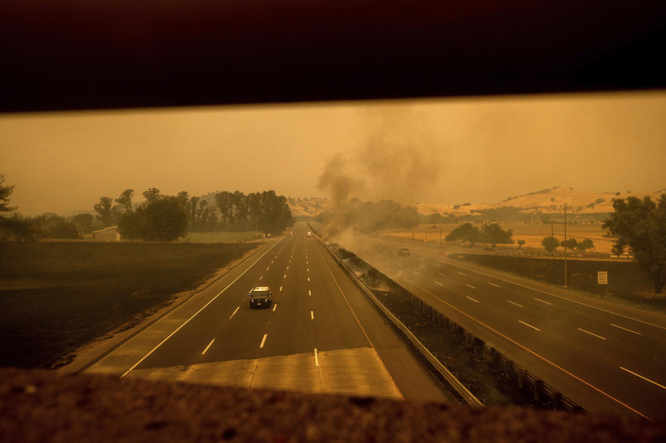 A police vehicle drives along Interstate 80, which was closed when flames from the LNU Lightning Complex fires jumped the roadway, in Vacaville, Calif., on Wednesday, Aug. 19, 2020. Fire crews across the region scrambled to contain dozens of wildfires sparked by lightning strikes. (AP Photo/Noah Berger)
