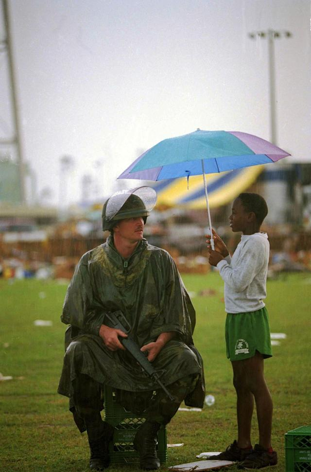 <p>Jerome Mitchell, 10, holds an umbrella as he chats with National Guardsman Toddy Bryan of Palmetto, Fla., at a food and clothing distribution center in Florida City, Fla., Aug. 30, 1992. Food and clothing are being given to victims of Hurricane Andrew. (AP Photo/Lynne Sladky) </p>