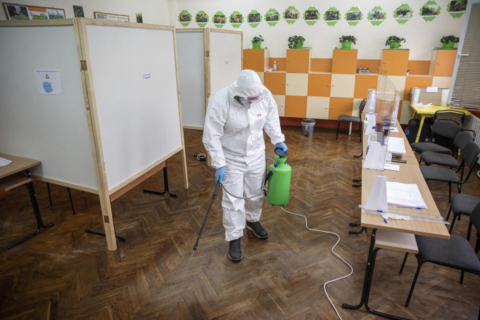 A health worker sprays disinfectant at a polling station during parliamentary elections in the town of during the parliamentary elections in the town of Bankya, Bulgaria, Sunday, April 4, 2021. Bulgarians are heading to the polls on Sunday to cast ballots for a new parliament after months of anti-government protests and amid a surge of coronavirus infections. (AP Photo/Visar Kryeziu)