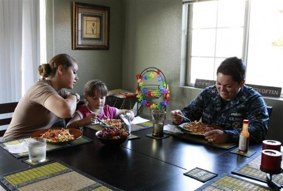 U.S. Navy Counselor 1st Class Luz Bautista, 30, who is four-months pregnant, (R) and her fiancee U.S. Navy Petty Officer 2nd Class Alejandra Schwartz, 24, (L) eat dinner with their daughter Destiny, 6, at their home in San Diego, California September 21, 2011. The 'Don't Ask, Don't Tell' law, which prevented serving US military personnel from disclosing that they were gay, was abolished. However, the military does not recognize same-sex marriage, and same-sex couples do not have the same benefits, or protection from being posted separately that heterosexual married couples in the military have. Bautista is being posted to Illinois for three years. The couple plans to pass the new baby to each other every few months, so she bonds with both mothers. But Bautista doesn't know when it will be possible for her to live with Alejandra and Destiny again.