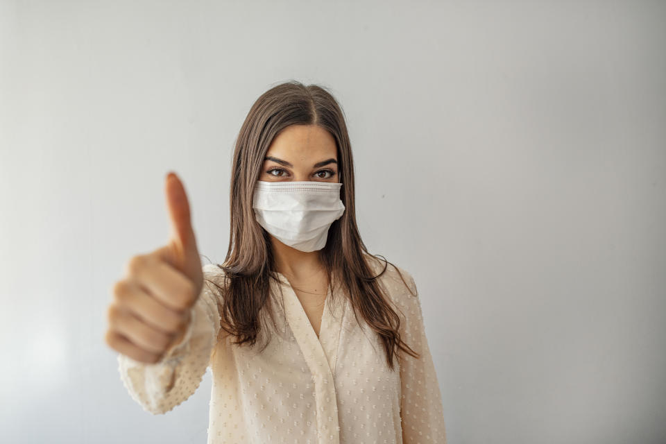 Portrait of young woman wearing face protective mask to prevent Coronavirus and anti-smog. Portrait of young woman wearing face mask. Thumb up.