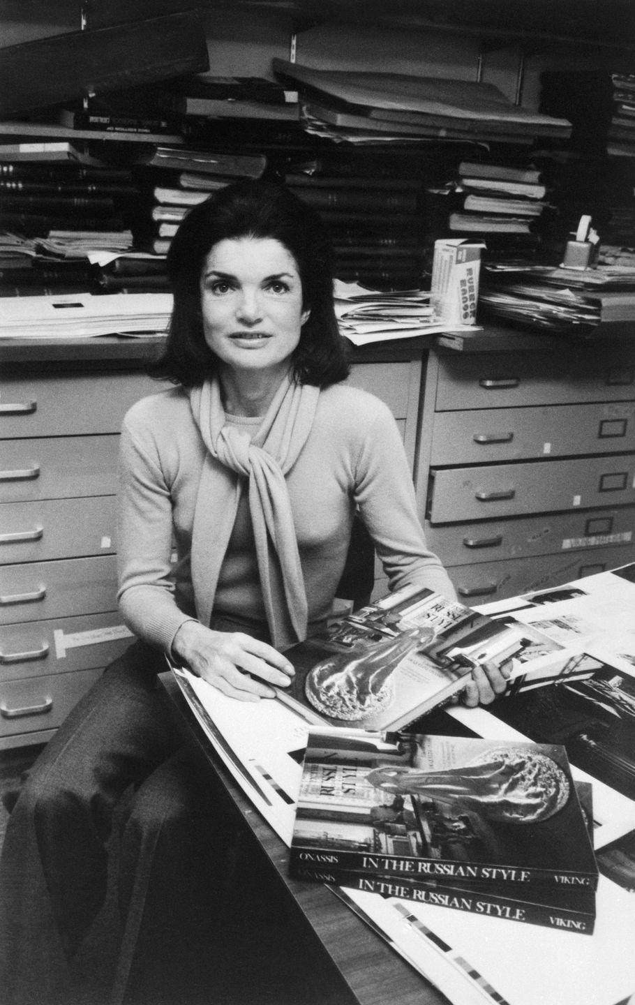 <p>Here, Jackie is photographed in her office at Viking Press, where she wrote and edited her first book <em>In the Russian Style</em>. She looks the part of a New York editor with a matching sweater set and flared tweed pants. <br></p>