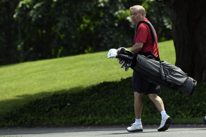 Senator Lindsey Graham, R-S.C., carries his golf clubs as he walks down the driveway of the White House in Washington, Sunday, June 16, 2019, after spending the day golfing with President Donald Trump. (AP Photo/Susan Walsh)