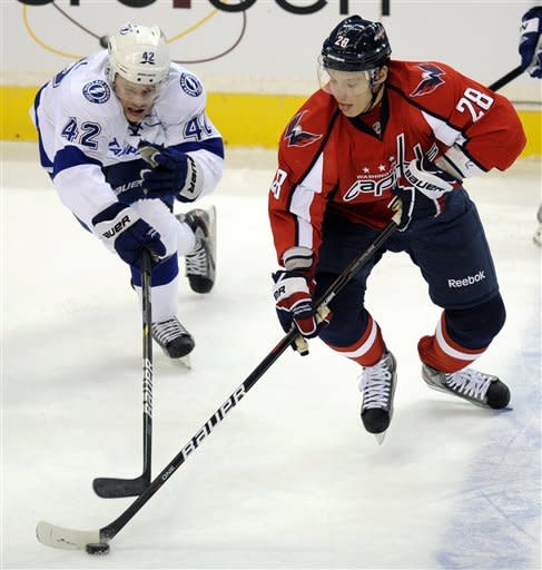 Tampa Bay Lightning center Dana Tyrell (42) battles for the puck against Washington Capitals left wing Alexander Semin (28), of Russia, during the first period of an NHL hockey game, Friday, Jan. 13, 2012, in Washington. (AP Photo/Nick Wass)
