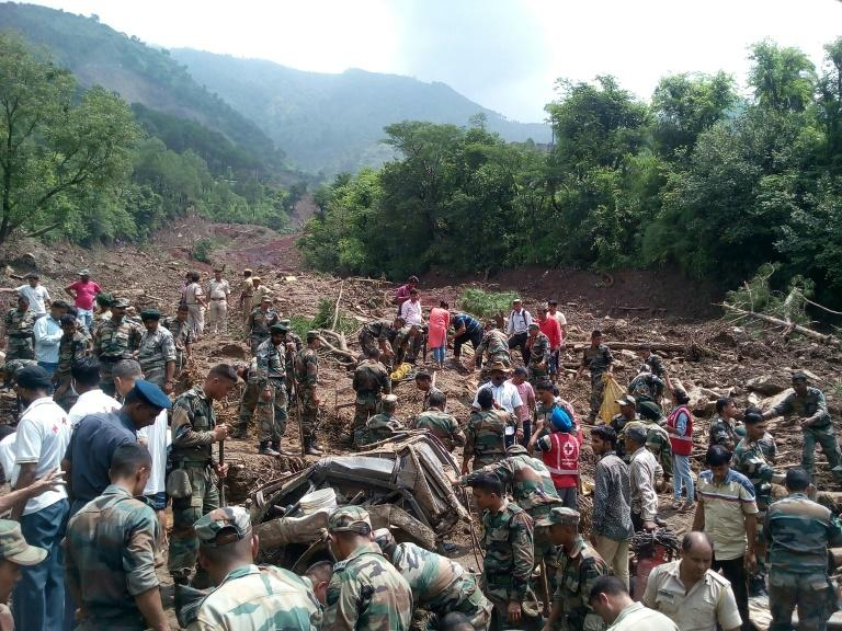 Rescuers look for survivors at the site of a landslide in Himachal Pradesh, northern India
