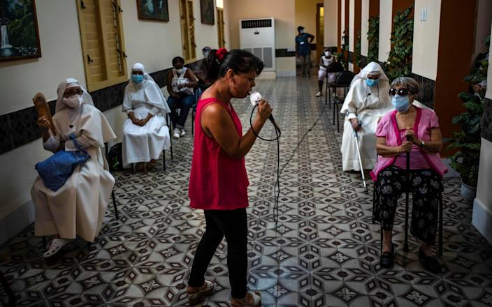 A woman sings for people that have just been inoculated with the Cuban Abdala Covid-19 vaccine, as they wait in the observation area in Havana, Cuba - Ramon Espinosa/AP