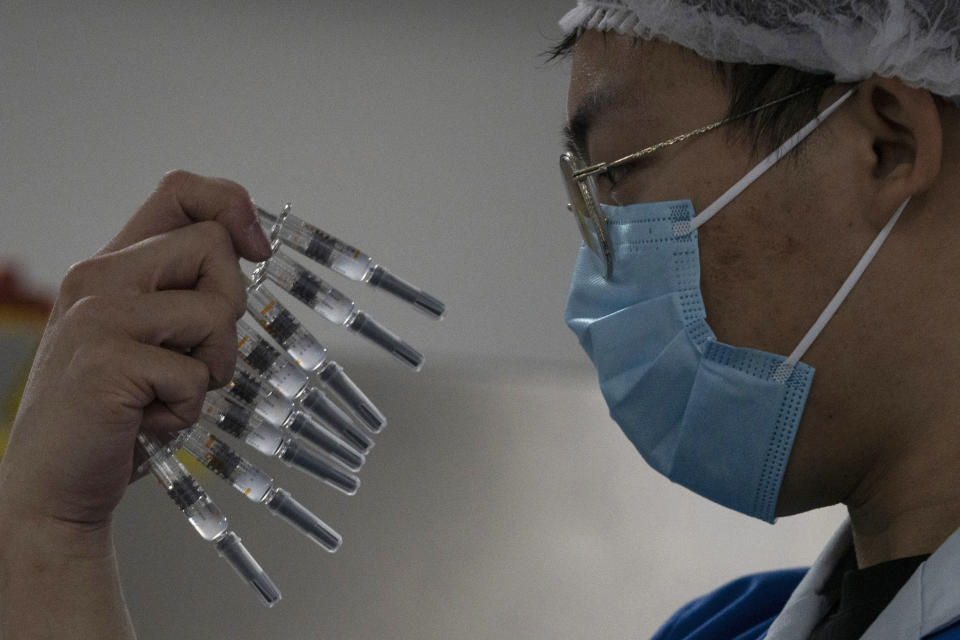 FILE - In this Thursday, Sept. 24, 2020 file photo, a worker inspects syringes of a vaccine for COVID-19 produced by Sinovac at its factory in Beijing. Sinovac and Sinopharm both rely on a traditional technology called an inactivated virus vaccine, based on cultivating batches of the virus and then killing it. (AP Photo/Ng Han Guan)