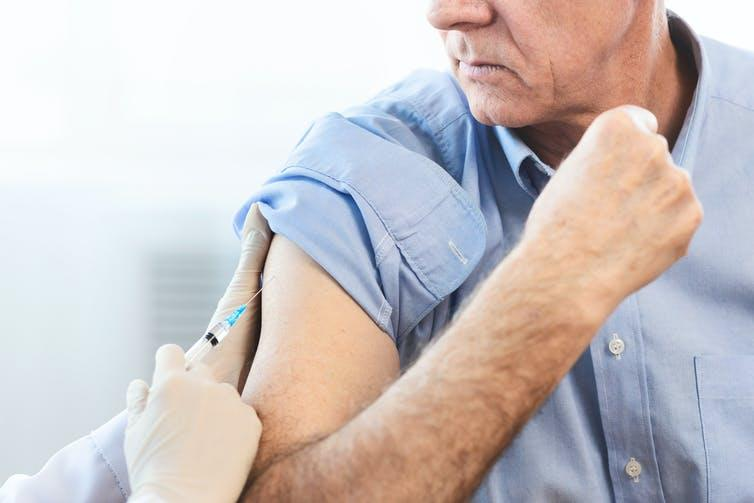 Older man receiving a vaccination.