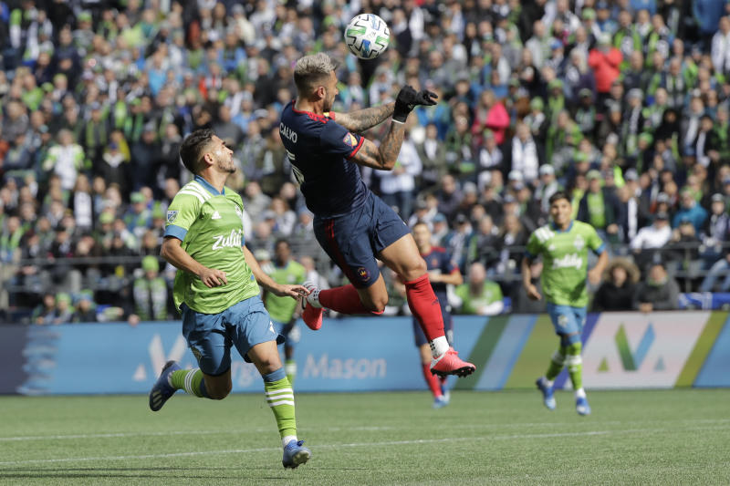 Chicago Fire defender Francisco Calvo, center, heads the ball in front of Seattle Sounders midfielder Cristian Roldan, left, during the first half of an MLS soccer match, Sunday, March 1, 2020, in Seattle. (AP Photo/Ted S. Warren)