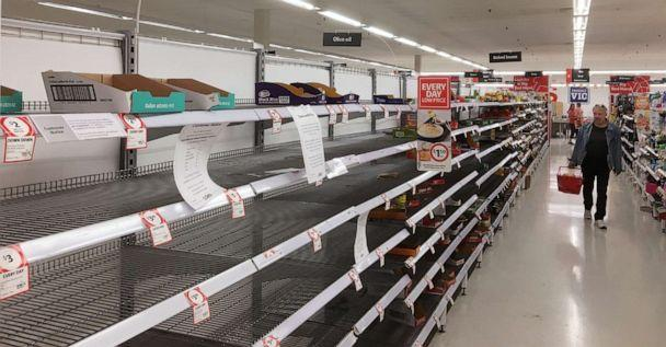 PHOTO: Shoppers walk down the aisles with empty shelves in a supermarket in Ivanhoe, Melbourne, Australia, March 16, 2020. (Picture Alliance via Newscom)