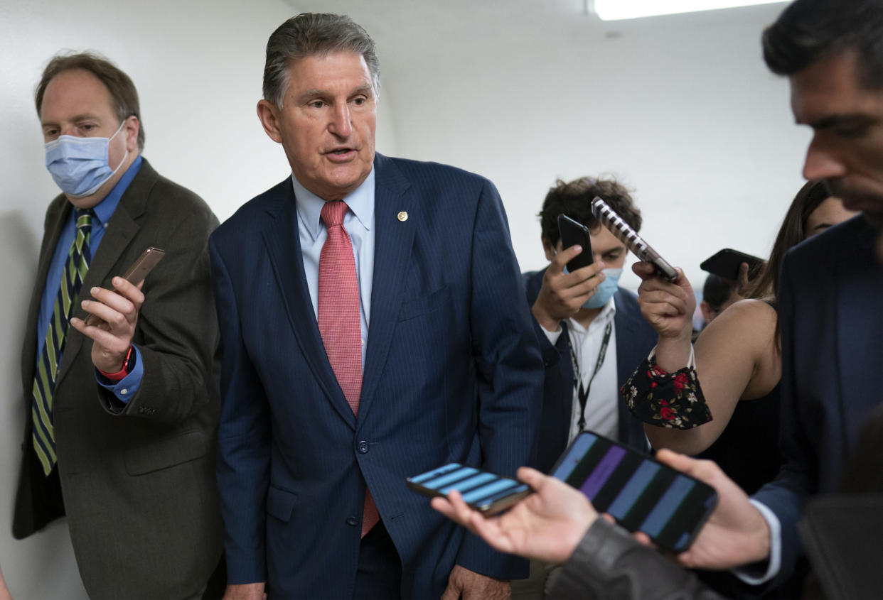 Sen. Joe Manchin, D-W.Va., is surrounded by reporters as senators rush to the chamber for votes ahead of the approaching Memorial Day recess. (J. Scott Applewhite/AP)