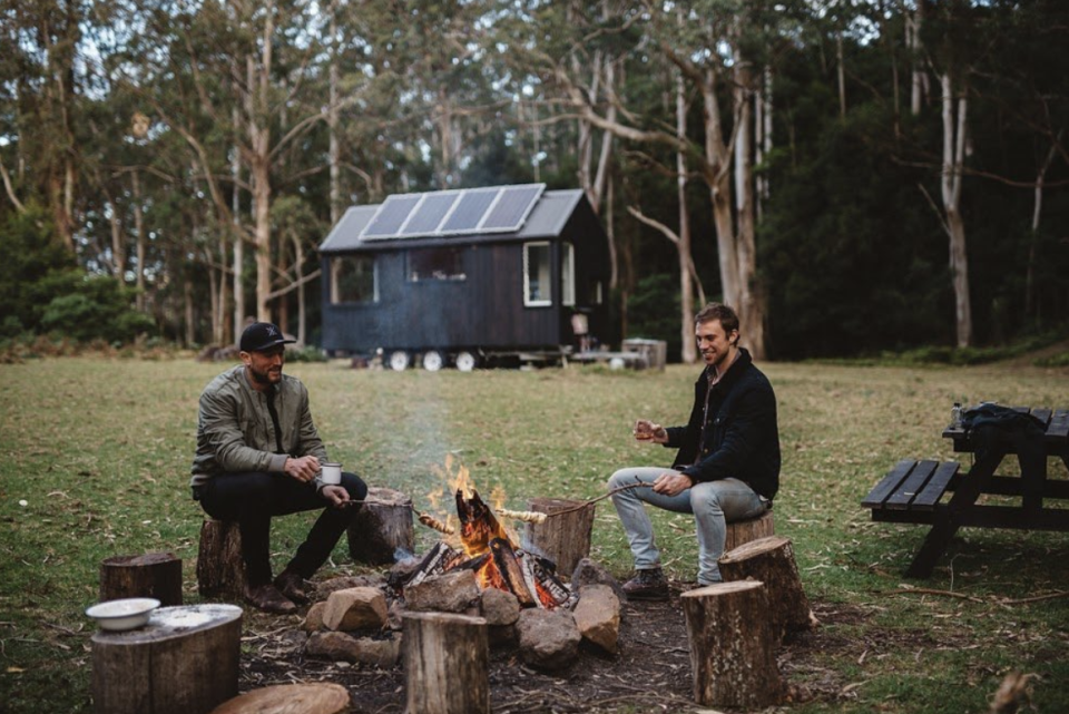Two men sit around a campfire with an Unyoked cabin in the background