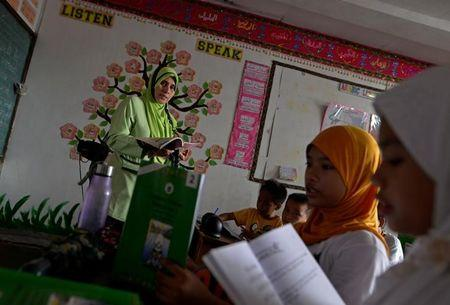 "Zainab Omar, 41, teacher, from Taguig city, teaches her pupils Koranic verses at a religious school in Taguig city, Metro Manila, Philippines October 14, 2016. ""The children are safer now. Parents used to accompany their children to school before Duterte sat as president. Now they let their children go to school by themselves,"" she said. REUTERS/Ezra Acayan"